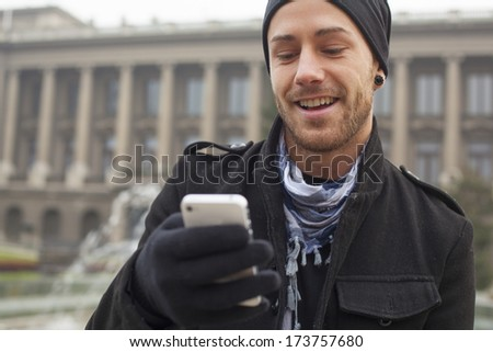 Traveling Man With Mobile Phone And Hat, In City, Urban Space - stock photo