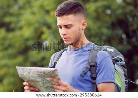 Traveling. Portrait of a young handsome tourist wearing blue t-short and backpack standing and looking seriously at the map in his hands - stock photo