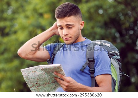 Traveling. Portrait of a young handsome tourist wearing blue t-short and backpack standing, feeling lost scratching head and looking at the map in his hand - stock photo