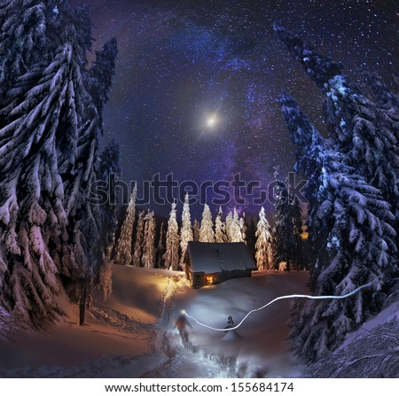 Traveling through the winter mountains, bold and romantic people can find shelter in the hunting huts, Glued to the panorama at a slow. The Milky Way as smoke rises over the frozen nature... - stock photo