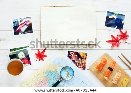 Traveling to Japan / memories of Japan concept. Japan view travel photo, map, sushi set, green tea, red maple leaf on a white table. Copy space. - stock photo