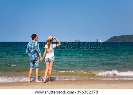 Traveling together: young couple on a tropical beach in Asia - stock photo