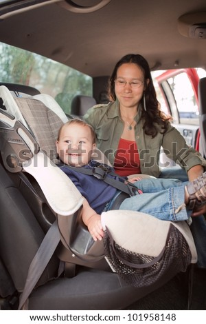 Traveling with a baby. Mother & baby in the back seat of a car on a road trip. - stock photo