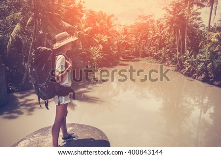 Traveling woman standing with backpack and straw hat near tropical lake (intentional sun glare and vintage color) - stock photo