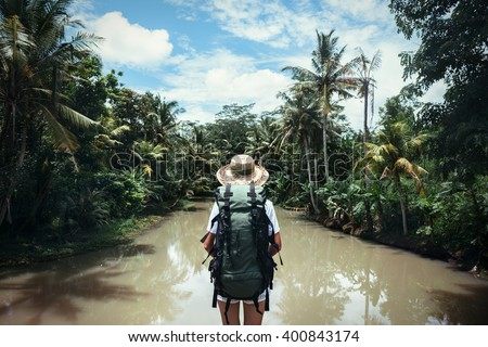Traveling woman with backpack and straw hat looking at tropical river at sunny day - stock photo