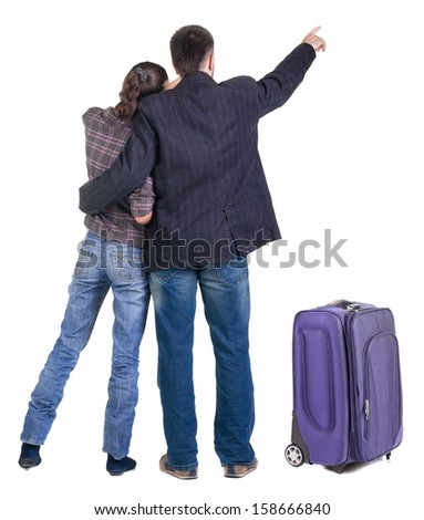 traveling young couple with suitcas pointing at wall. Back view people. Isolated over white background. - stock photo