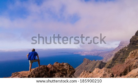 traveller looking over the west coast of Gran Canaria - stock photo