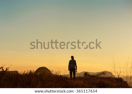 Traveller with an ax near the tent on a mountain top - stock photo