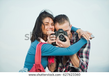 Travelling and wanderlust. Happy girl or beautiful woman hugging handsome man, photographer, photographing with camera. Romantic couple in love on idyllic summer vacation