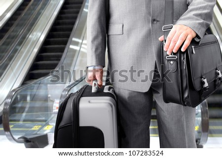 Travelling Businessman.  Businessman with his luggage near an escalator at an airport - stock photo
