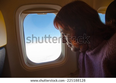 Travelling by air - woman is sitting in the airplane looking  through window - stock photo