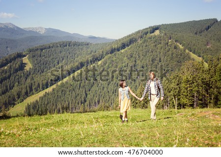 Travelling couple walking together at the summer meadow and looking around mountain view