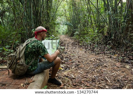 Travelling man sitting and looking at the map in the bamboo forest - stock photo