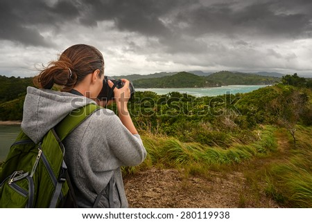 Travelling woman photographer with backpack  making an inspiring landscape of dramatic clouds. Tourist girl traveling along Asia, active lifestyle concept - stock photo