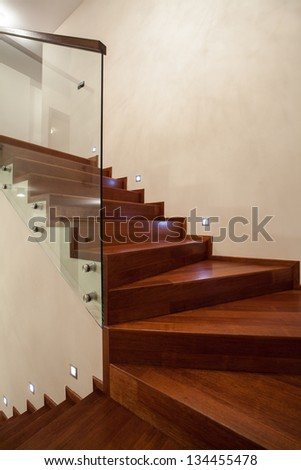 Travertine house- Closeup of wooden, glass stairs in modern interior - stock photo