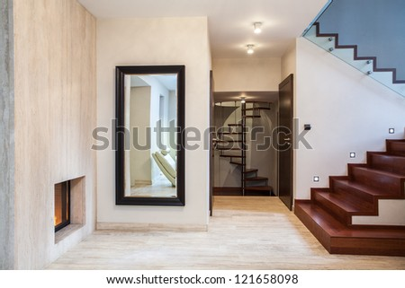 Travertine house: huge mirror and wooden stairs - stock photo