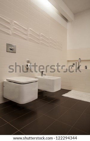 Travertine house - toilet and bidet in a cosy bathroom - stock photo