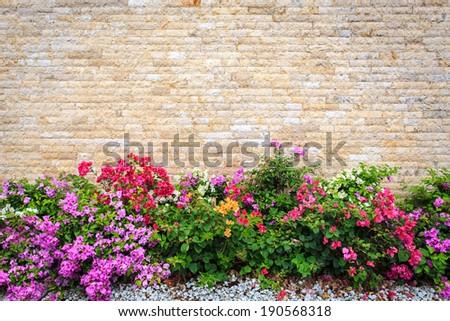 Travertine stone wall and decorative garden - stock photo