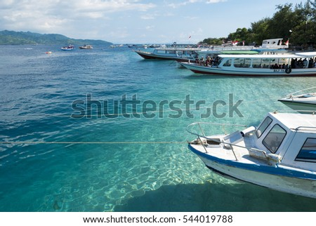 TRAWANGAN ISLAND, INDONSIA, MARCH 25: Harbor of Trawangan Island  with moored small boats, tourists and turquoise sea water of Gili islands, Bali, Indonesia 2016