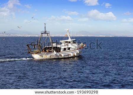 Trawler fishing boat working close to Alicante coast - stock photo