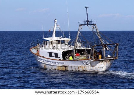 Trawler fishing boat working in open waters - stock photo