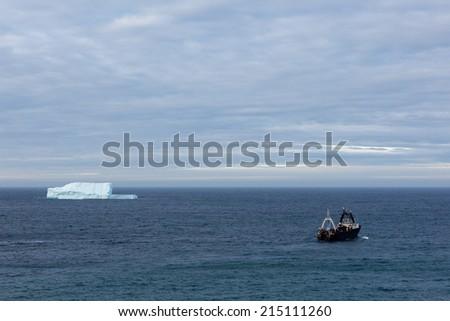Trawler leaving port and passing iceberg. - stock photo