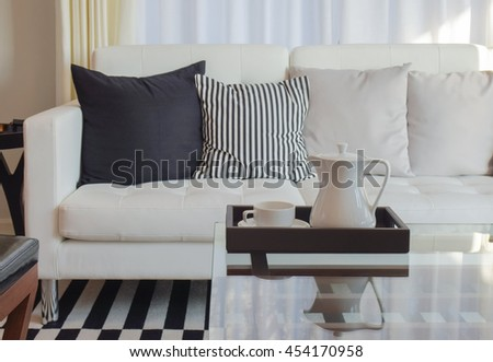 Tray of afternoon tea on glass top table with black and white pillows on sofa in background