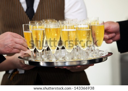 Tray of chilled champagne in elegant flutes being carried by a waiter at a catered event with male hands helping themselves to a glass