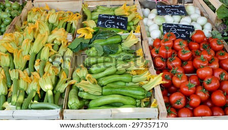 Tray of fresh zucchini with flowers and tomatoes at a farmers market