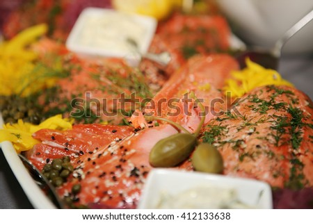 Tray of gourmet smoked salmon with sauce and pickled garnish.