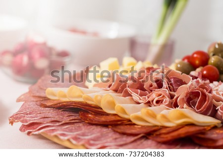 Tray with bacon, cheese cubes, salami, ham; with spring onions in the background