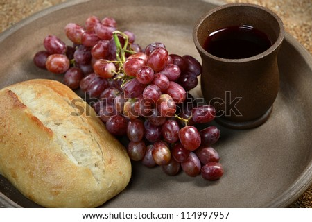 Tray with bread, red grapes and cup of wine symbolizing the body and blood of Christ