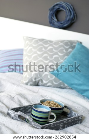 Tray with breakfast on a bed - stock photo