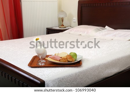 tray with breakfast on bed - stock photo