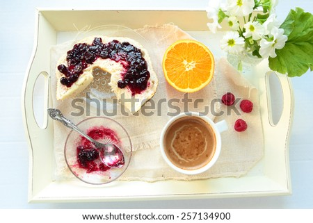 Tray with breakfast. Roll with currant jam and cup of coffee - stock photo