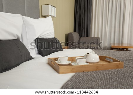 Tray with coffee on a bed in a hotel room - stock photo