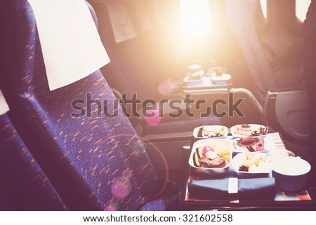Tray with delicious healthy food on the plane, business class travel. Tasty Lunch served in the aircraft interior. Sun shining through the airplane window. Lens Flare. - stock photo