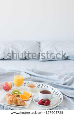 Tray with healthy breakfast on a bed with gray bed linen. Copy space. - stock photo