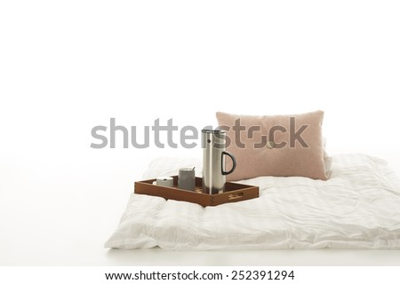 Tray with hot coffee on a soft plain white down comforter with beige cushion lying on a white studio background with copyspace in a minimalist interior design or decor - stock photo