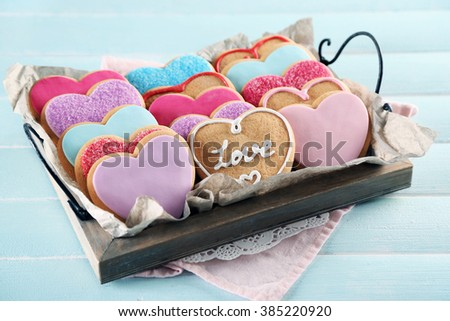 Tray with love cookies on blue wooden table background - stock photo
