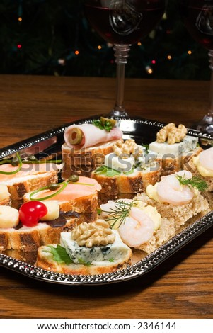 Tray with sandwiches on holiday table with wine and Christmas tree with lights on background - stock photo