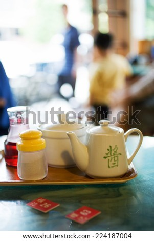 Tray with tea service and table markers on table in restaurant - stock photo