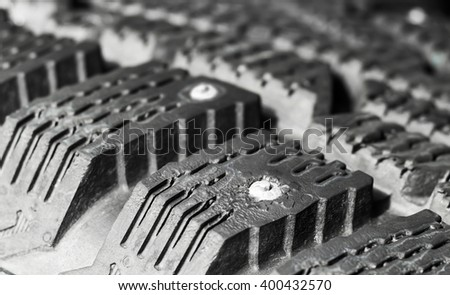 Tread winter car tire with spikes close-up - stock photo