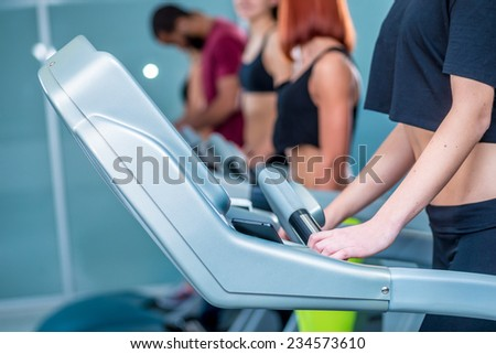 Treadmill closeup. Sport and slender girl running on a treadmill. Athlete dressed in sports uniforms and running in the gym. - stock photo