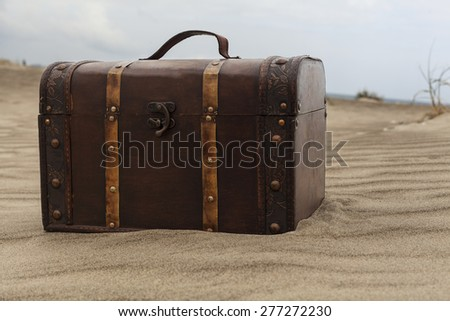 Treasure chest in sand dunes on the beach - stock photo