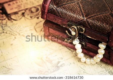 Treasure chest with coins and pearls jewelry over ancient map - stock photo