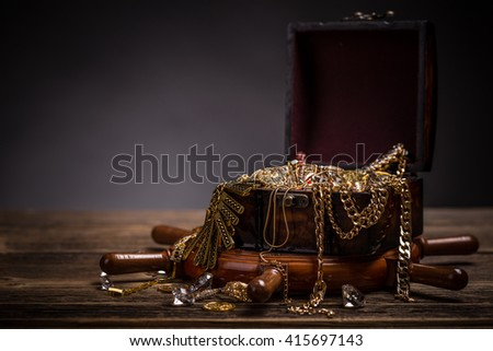 Treasure chest with jewellery on wooden background