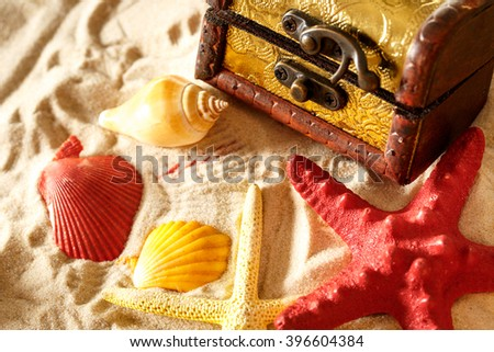 Treasure chest with seashells on sand background - stock photo