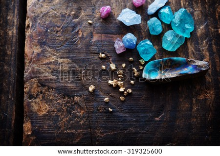 Treasure hunting. Mining for gems. Gold and gems on rough wooden surface. - stock photo