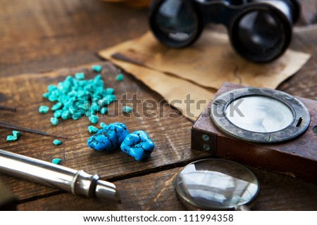 Treasure hunting, or gem stone hunting. A compass, magnifying glasses and turquoise stones on a old wood desk. - stock photo
